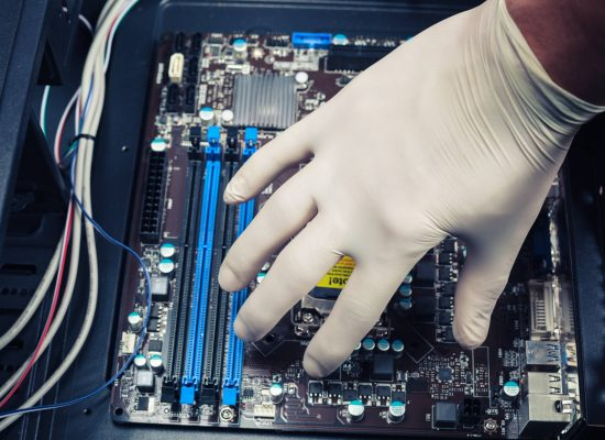 A hand wearing a rubber glove is installing computer components